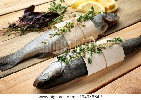 Fresh trout fish wrapped in paper on wooden background