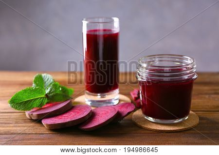 Antioxidant beet smoothies with sliced beetroot and mint on wooden table