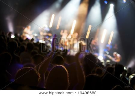 Big crowd of fans listening to live concert of pop band on stage, soft focus.