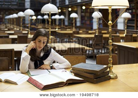 Young attractive student sitting at desk in old university library studying books.