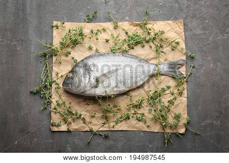 Parchment with fresh dorado fish and thyme on gray background