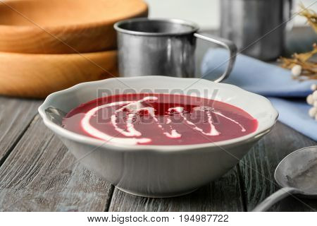 Delicious beet soup with sour cream in bowl on kitchen table