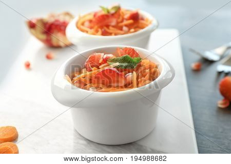 Cute white bowl with yummy carrot strawberry salad on marble board