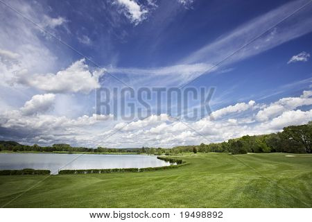 Beautiful golf course with lake, fairway and beautiful cloud formation.