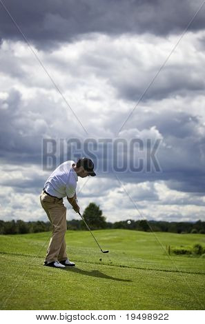 Golf player pitching the golf ball, ball in the air.