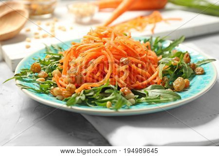 Blue plate with delicious carrot raisin salad with arugula on table, closeup