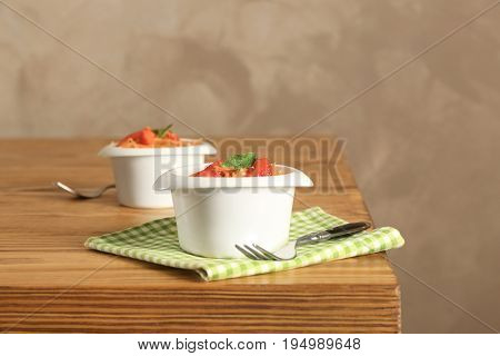 White bowls with yummy carrot strawberry salad on wooden table