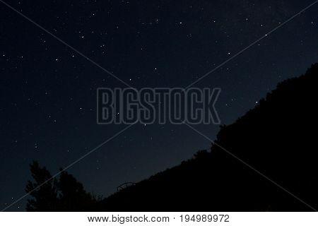 Noche estrellada con montañas haciendo de siluetas