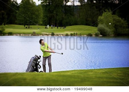 Golf player pitching golf ball at lake with ball in the air.