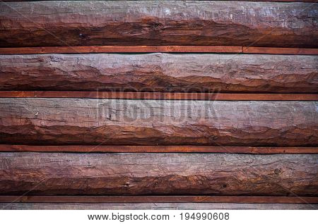 A background with horizontal round balks with rough brown dark varnished surface and with insertions between balks