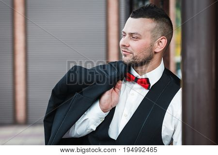 Young stylish man in a suit. Portrait of the groom. The groom is holding his jacket on his shoulder side view groom looking to the side
