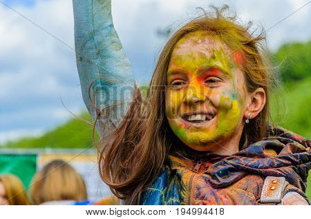 Moscow, Russia - June 3, 2017: Girl child sincerely enjoys what is happening at the Holi color festival. Traditional summer Indian festival Holi turned into a fun event in many countries of the world