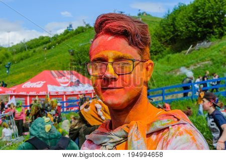 Moscow, Russia - June 3, 2017: Portrait of a young hipster-boy in glasses after a colorful headshot at Holi color festival. Happy red face. Summer Holi turned into a fun event in many countries