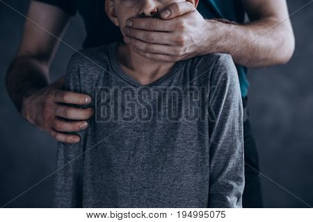 Scary conceptual photo of terrified kidnapped boy