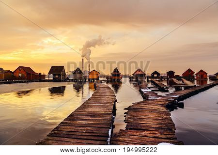Sunset lake Bokod with pier and fishing wooden cottages power plant in background Hungary