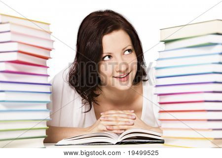 Close up of pretty smiling girl lying on floor between two stacks of colorful books reading and looking up, isolated on white background.