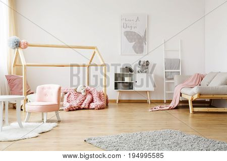 Spacious fully furnished girl's room with creative bed and bright sofa