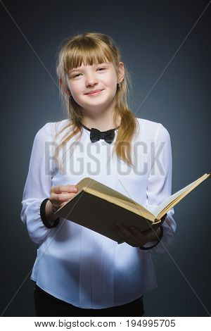 Handsome little girl with book smiling isolated on gray background.