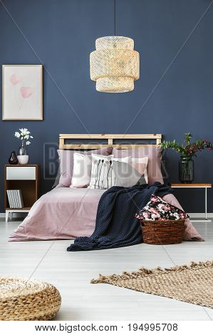 Dark walled room with decorative cushions and blue blanket on wooden bed
