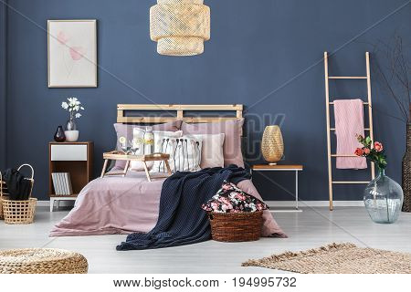 Wooden breakfast tray with two glasses and bottle standing on king-size bed