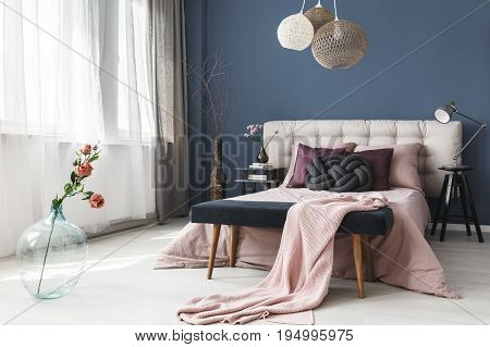 Pink fresh roses in big glass vase standing in elegant cozy bedroom