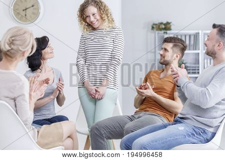 Girl getting applause during support group meeting