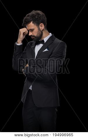 Handsome Bearded Upset Businessman In Bow Tie And Black Suit, Isolated On Black