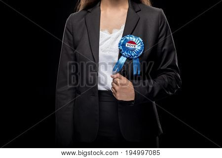 Cropped View Of Businesswoman In Black Suit With Vote Badge, Isolated On Black