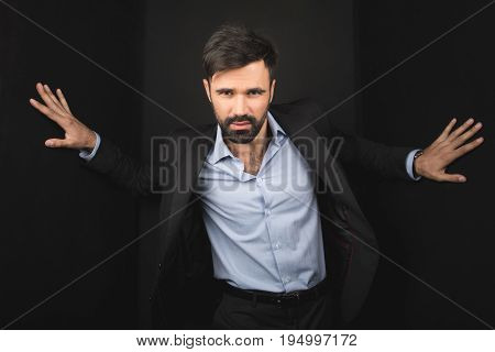 Handsome Confident Businessman Posing In Black Suit, Isolated On Black