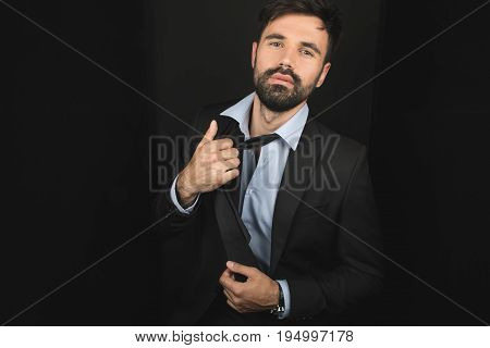 Handsome Bearded Businessman Posing In Tie And Black Suit, Isolated On Black