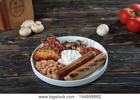 Healthy Full English Breakfast - plate with poached eggs, sausages, mushrooms, toasts and bacon on wood background