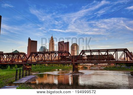 A train races across the bridge in front of the Columbus, Ohio skyline as seen from Northbank Park.