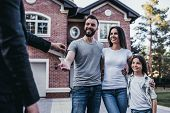 Happy family is taking keys from their new house from broker and smiling. poster