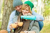 Happy couple in nature drinking tea outdoors having picnic in fall season smiling laughing poster