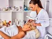 Eyebrow treatment of woman middle-aged in spa salon. Tweezing eyebrow by beautician. 40s old female under cosmetic lamp. European facial procedure. Patient looking up. Medical professional room poster