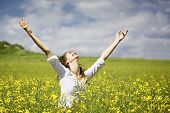 Young woman standing in yellow rapeseed field raising her arms expressing gratitude or freedom. poster