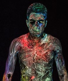 Shirtless man standing with glowing UV powder and liquid on him lit using ultraviolet blacklight