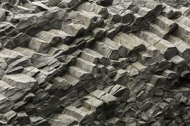 Texture of interesting and colorful Icelandic basalt rock columns
