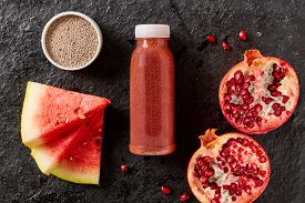 Healthy organic pomegranate and watermelon smoothie with chia seeds liquidised and served in a bottle surrounded by the fresh ingredients viewed from overhead
