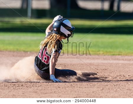 Female Teenage Softball Player In Black Uniform Sliding Safely Into Second Base.