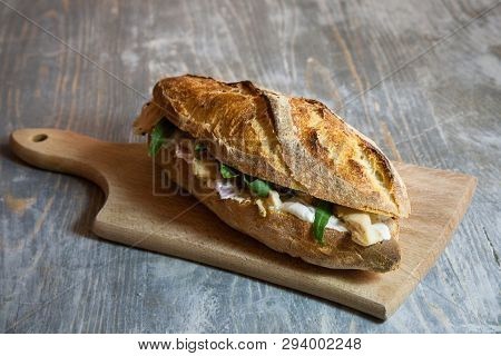Brie Sanwdich In A French Baguette, Made Of Brie De Meaux Cheese With Some Slices Of Rucola Salad An