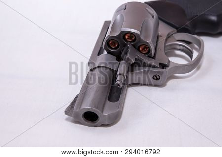 A stainless steel snub nosed 357 magnum revolver loaded with hollow point bullets on a white background poster