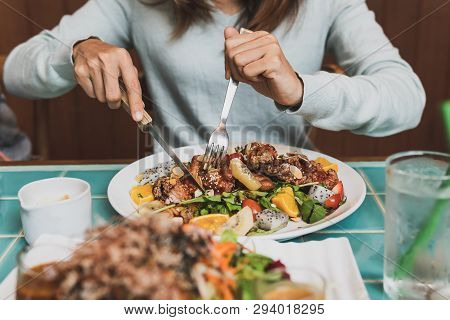 Young Woman Using Knife And Fork To Cutting Meat In Restaurant