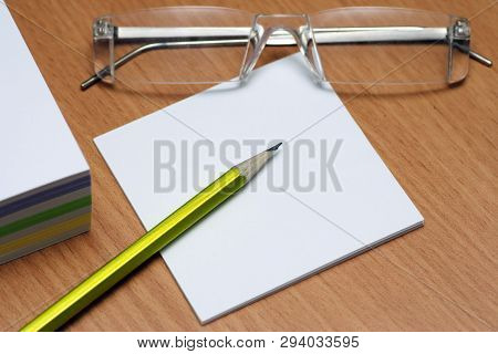 Adhesive Note With Pencil And Eyeglass On Desk