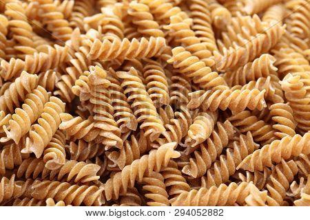 Raw Brown Pasta (fusilli) Background. Close Up.