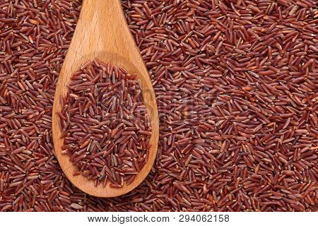 Red Rice In A Wooden Spoon On Red Rice Background.