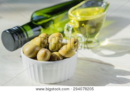 Glass Sauceboat With Extra Virgin Olive Oil,  Fresh Green Olives And Bottle On Wooden Table.
