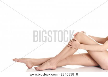 Female smooth legs sitting on white background. Depilation skin concept.