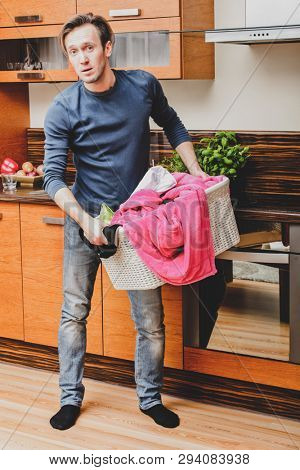 Man standing in kitchen with laundry basket in hands. Housework concept.