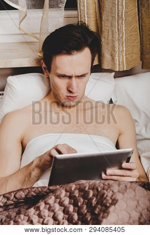 Man lying in bed with tablet in hands and browsing news on it, inside home.
